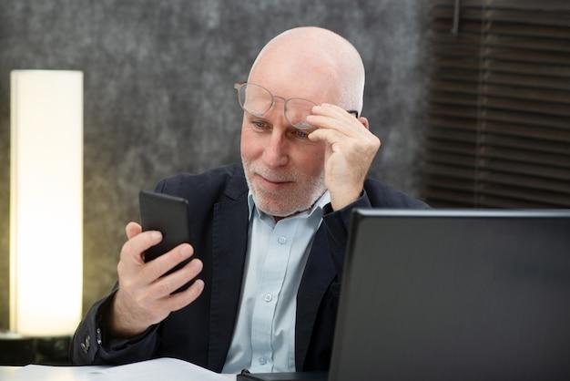 Empresario senior usando un teléfono inteligente, tiene dificultades y problemas de visión.