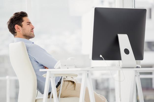 Empresario sentado con los brazos cruzados en la oficina