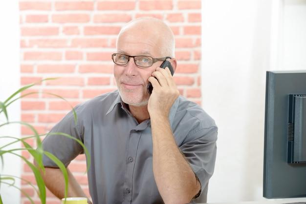 Empresario sentado en el escritorio y hablando por celular