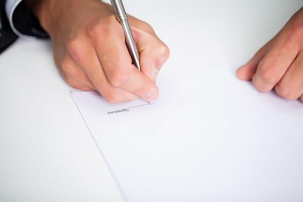 Empresario sentado en el escritorio de oficina firmando contrato
