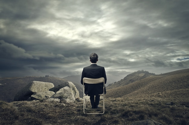 Empresario sentado en una silla en la montaña