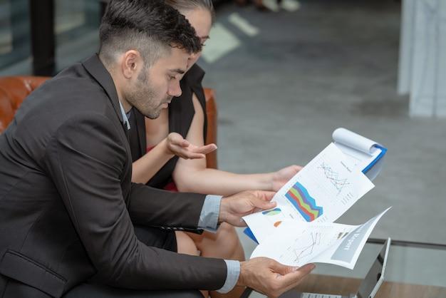 Empresario serio y empresaria reunidos juntos buscando informe financiero resumen de negocio en la oficina