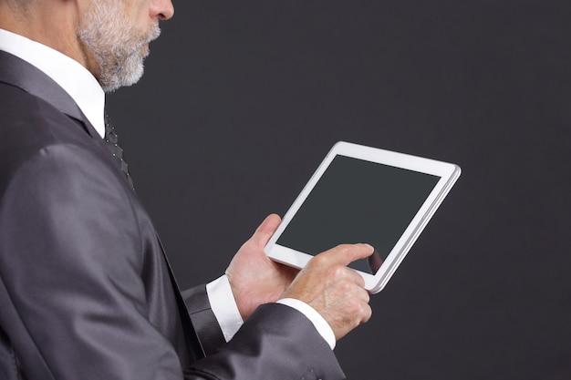 Empresario serio mirando la pantalla de la tableta digital.