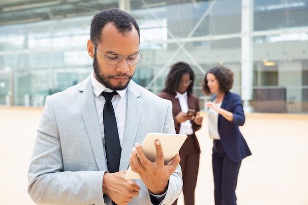 Empresario serio usando tableta afuera