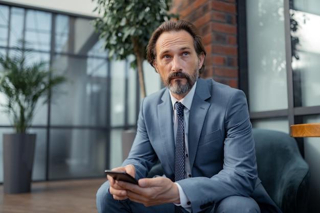 El empresario se siente pensativo. apuesto hombre de negocios próspero que se siente pensativo mientras espera la reunión