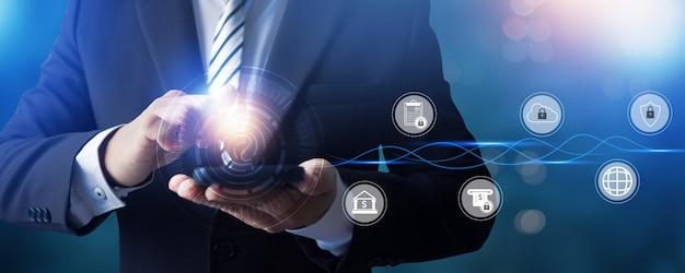 Empresario con smartphone con diseño de iconos de seguridad digital sobre fondo azul.