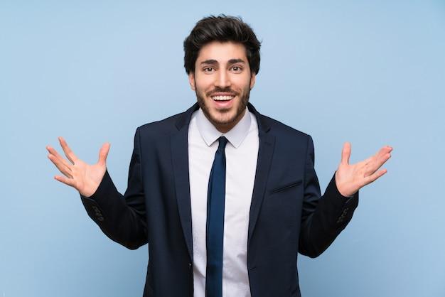 Empresario sobre pared azul aislada con expresión facial sorprendida
