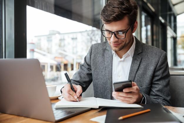 Empresario sonriente en anteojos sentado junto a la mesa en la cafetería con computadora portátil mientras usa el teléfono inteligente y escribe algo
