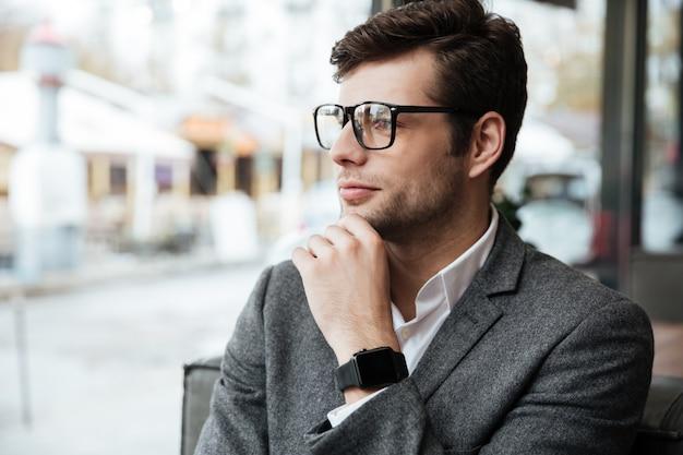 Empresario sonriente en anteojos sentado junto a la mesa en la cafetería y mirando a la ventana