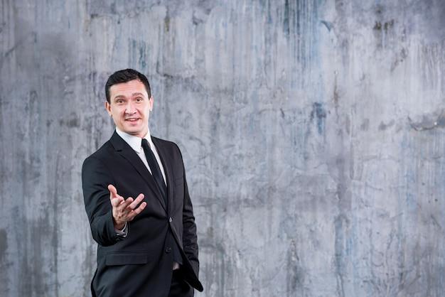 Empresario sonriente apuntando a la cámara mientras está de pie contra la pared gris