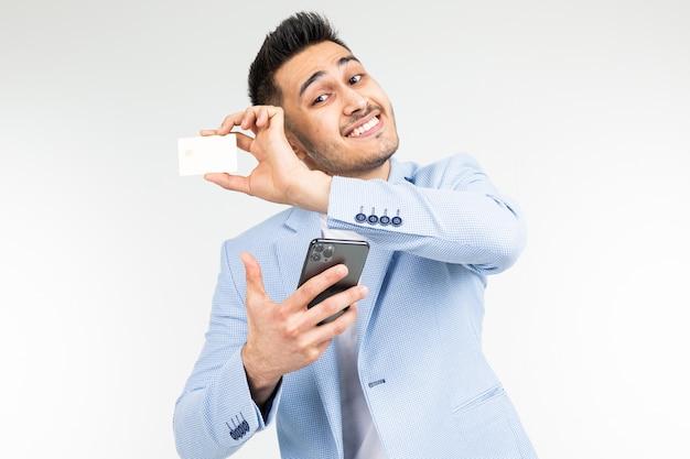 Empresario sonriente en una chaqueta azul con una tarjeta de crédito con una maqueta y un teléfono inteligente en la mano sobre un fondo blanco de estudio