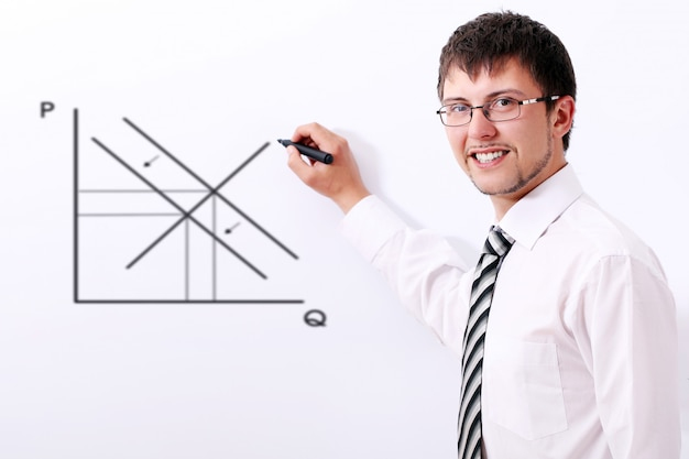 Empresario sonriente dibujando el gráfico de oferta y demanda