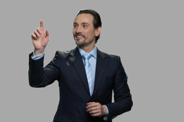 Empresario sonriente mediante interfaz invisible. gerente guapo trabajando en pantalla virtual sobre fondo gris.