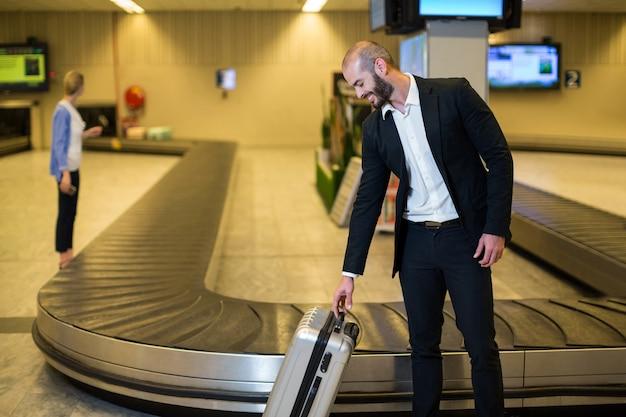 Empresario sonriente con maleta en la zona de espera