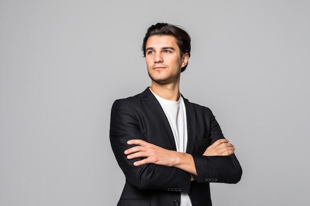 Empresario sonriente de pie con los brazos cruzados aislado en un blanco