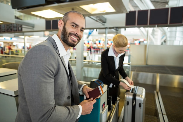 Empresario sonriente de pie con pasaporte mientras el asistente se pega la etiqueta al equipaje