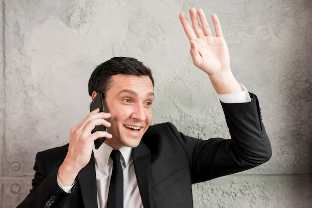 Empresario sonriente saludando con la mano y charlando en el teléfono