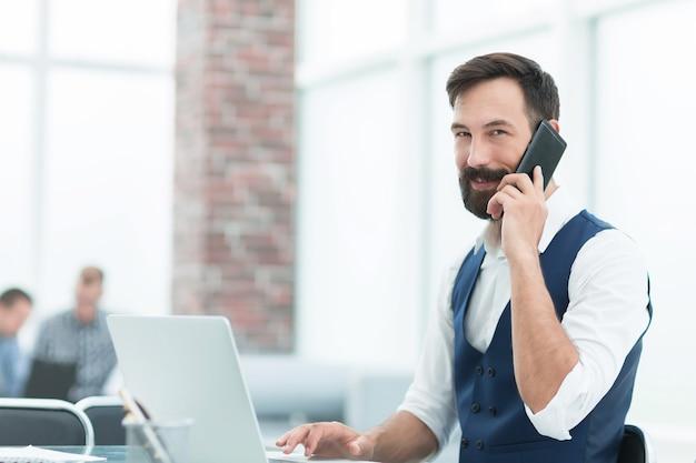 Empresario sonriente sentado en su escritorio en la oficina, personas y tecnología.