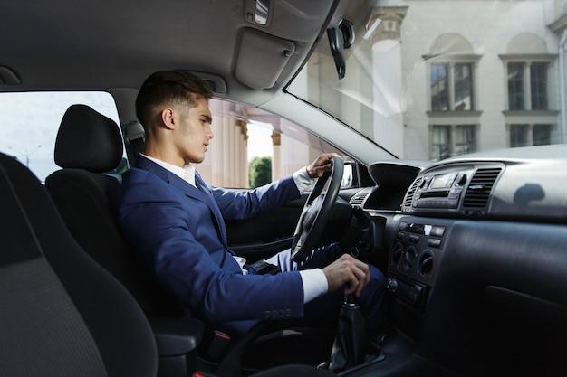 Empresario sonriente se sienta en el coche