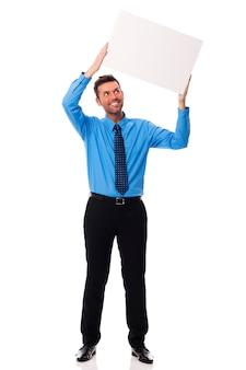 Empresario sonriente sosteniendo cartel en blanco
