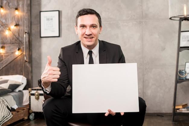Empresario sonriente sosteniendo papel en blanco y gesticulando pulgar arriba