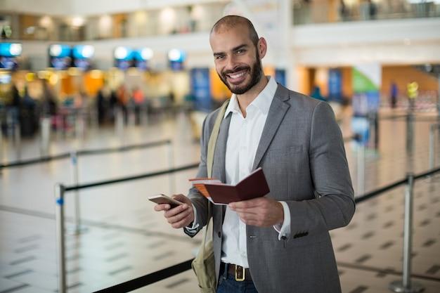 Empresario sonriente sosteniendo una tarjeta de embarque y comprobando su teléfono móvil