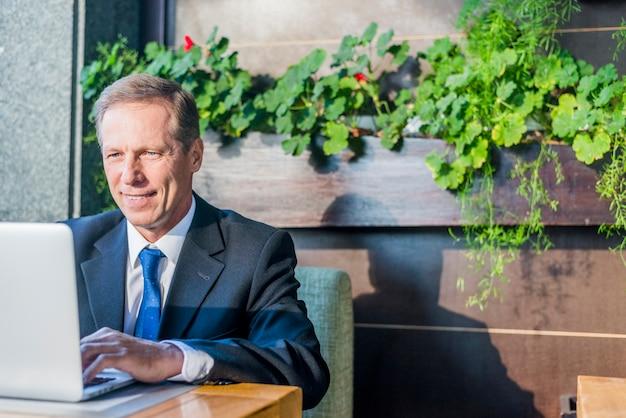 Empresario sonriente usando laptop en restaurante