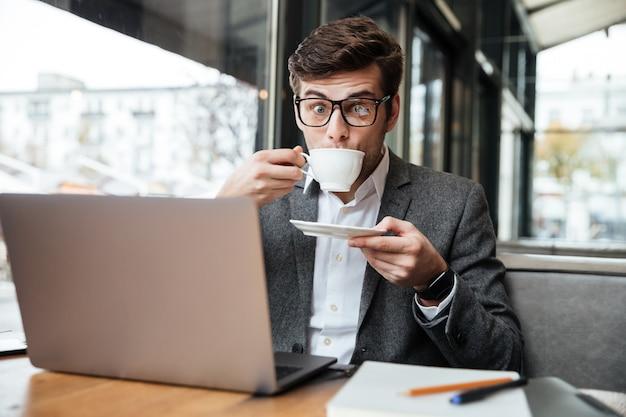 Empresario sorprendido en anteojos sentado junto a la mesa en la cafetería con computadora portátil mientras bebe café y mira