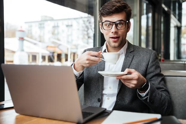 Empresario sorprendido en anteojos sentado junto a la mesa en la cafetería con computadora portátil mientras sostiene una taza de café y mirando