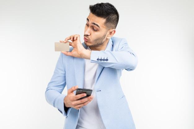 Empresario sorprendido en una chaqueta azul con una tarjeta de crédito con una maqueta y un teléfono inteligente en la mano sobre un fondo blanco de estudio