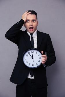 Empresario sorprendido sosteniendo el reloj de pared sobre pared gris