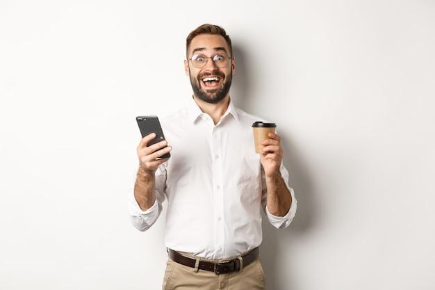Empresario sorprendido tomando café, reaccionando a la impresionante oferta en línea en el teléfono móvil, de pie sobre fondo blanco.