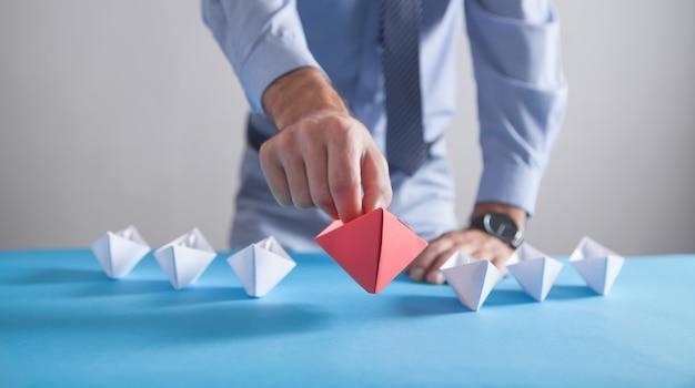 Empresario sosteniendo un barco de papel de origami rojo con barcos blancos. negocios, liderazgo