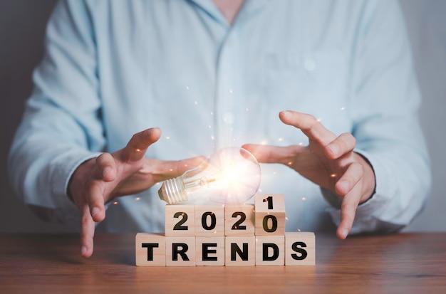 Empresario sosteniendo la bombilla en la pantalla de impresión de tendencias de 2020 a 2021 en cubos de bloques de madera.