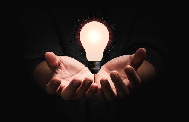 Empresario sosteniendo la bombilla que brilla intensamente con la línea de conexión para ideas de pensamiento creativo y concepto de innovación.