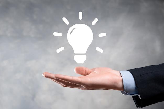Empresario sosteniendo bombilla. soluciones energéticas.