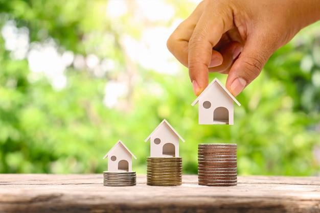Empresario sosteniendo casa modelo y casa modelo sobre un montón de monedas concepto de inversión inmobiliaria tasas de interés hipotecarias y de construcción de viviendas