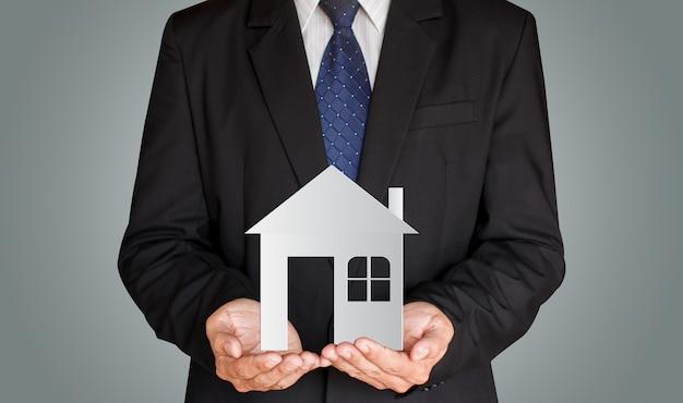 Empresario sosteniendo casa de papel en sus manos, concepto de bienes raíces