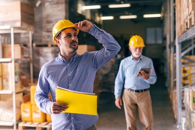 Empresario sosteniendo casco y carpeta con documentos mientras mira hacia arriba y de pie en el almacén