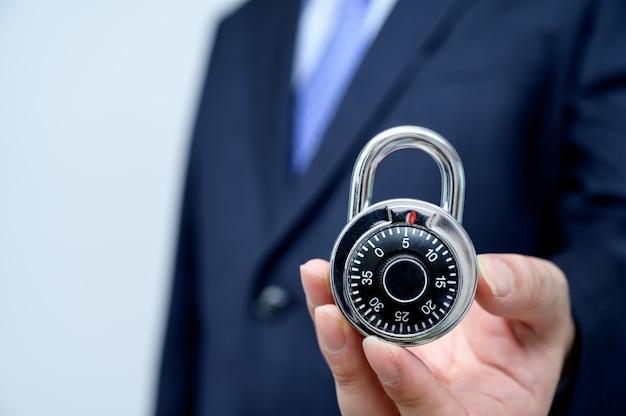 Empresario sosteniendo una cerradura.