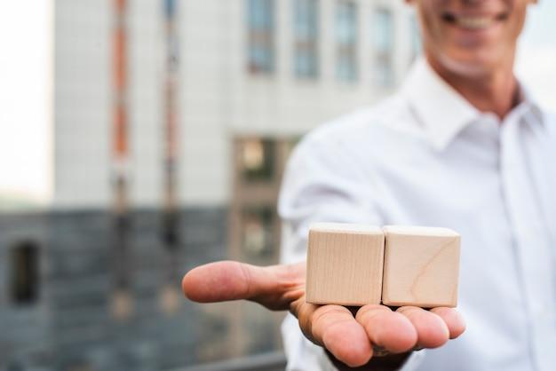 Empresario sosteniendo cubos en la mano