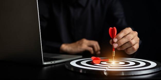 Empresario sosteniendo dardos apuntando al concepto de objetivo empresarial del centro de destino -