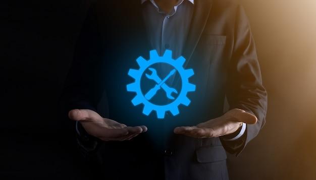 Empresario sosteniendo el icono de engranaje con herramientas. engranajes. concepto de diagrama digital de enfoque de destino, interfaces gráficas, pantalla de interfaz de usuario virtual, red de conexiones.