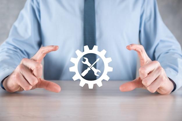 Empresario sosteniendo el icono de engranaje con herramientas