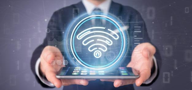 Empresario sosteniendo un ícono de wifi con estadísticas y código binario