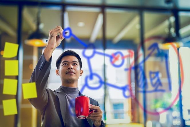 Empresario sosteniendo la taza de café y escribiendo datos en tablero transparente