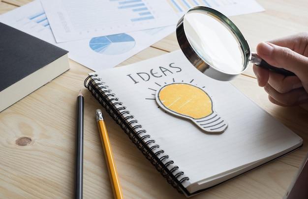 Empresario sosteniendo lupa con bombilla. concepto de ideas de creatividad empresarial.