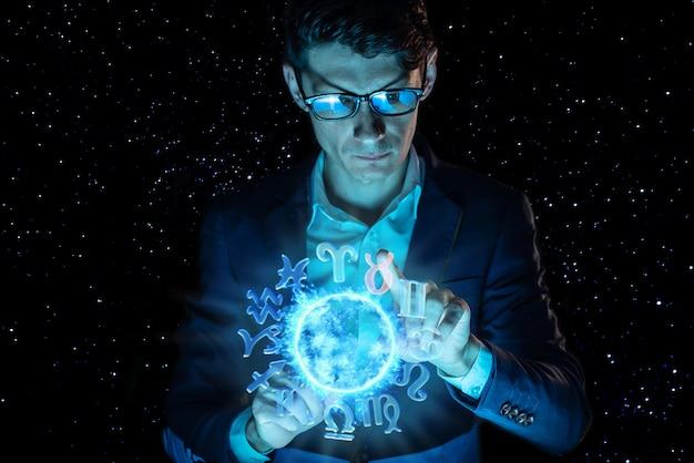 Empresario sosteniendo la mano sobre la esfera mágica con un horóscopo para predecir el futuro. la astrología como negocio.