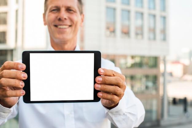 Empresario sosteniendo maqueta de tableta