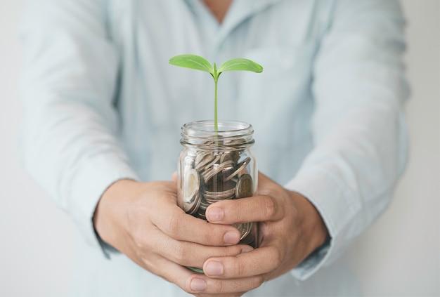 Empresario sosteniendo monedas en una alcancía con planta de crecimiento, ganancias de inversión y dinero de dividendos del concepto de ahorro.